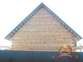 Вид на деревянный дом из бруса со стороны дороги