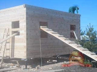 Работник бригады монтирует ряд стены брусового дома 6х6