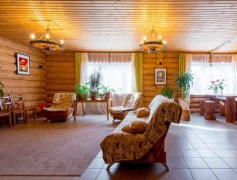 Гостиная комната в светлых тонах, рельеф бревен придает комнате необычность и своеобразие